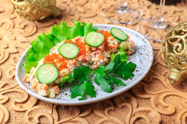 La classica insalata olivier viene servita sulla tavola festiva. presentazione originale. Foto Premium