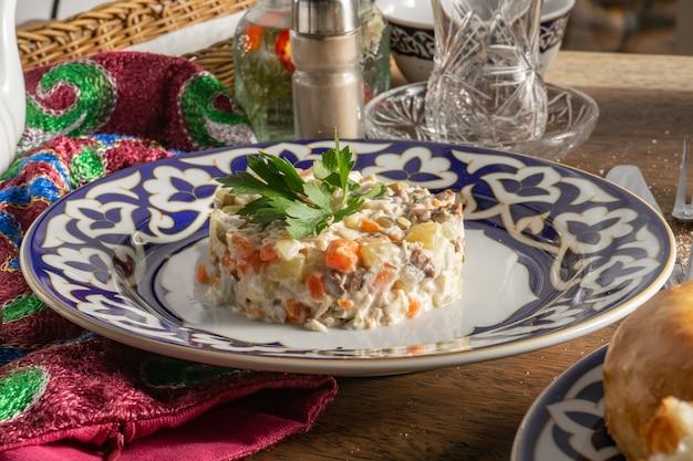 Insalata olivier classica con maionese, verdure e salsiccia decorata con prezzemolo in un piatto di ceramica con ornamenti tradizionali uzbeki su un tavolo di legno accanto alle posate con una forchetta e un coltello.