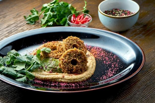 Un classico antipasto orientale - hummus di ceci con falafel, servito su un piatto nero su un tavolo di legno. cibo del ristorante