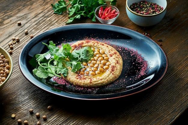 Un classico antipasto orientale - hummus di ceci con olio d'oliva bianco, servito su un piatto nero su un tavolo di legno. cibo del ristorante