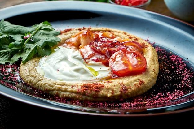 Un classico antipasto orientale - hummus di ceci con salsa bianca, cipolle caramellate, yogurt bianco e gamberetti, servito su un piatto nero su un tavolo di legno. cibo del ristorante