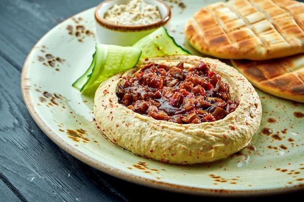 Un classico piatto orientale - hummus di ceci con verdure al forno e olio d'oliva servito con pita al forno in un tavolo di legno piatto