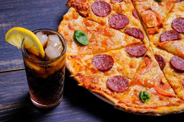 Pizza classica ai peperoni con salsa di pomodoro formaggio e salame su fondo di legno nero