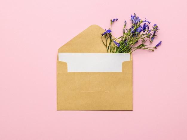 Una classica busta postale e un mazzo di fiori su sfondo rosa. disposizione piatta.