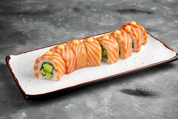 Rotolo di sushi classico drago rosso con avocado, salmone, frittata e salsa piccante su un piatto bianco su un tavolo grigio. messa a fuoco selettiva, granulosità del rumore sul post