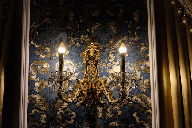 Lampadario in cristallo classico retrò a parete, sullo sfondo della carta da parati con la luce accesa.