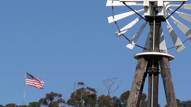 Classico mulino a vento retrò, rotore a lame e bandiera usa contro il cielo blu. turbina eolica della pompa dell'acqua dell'annata, generatore di corrente sul ranch del bestiame o sull'azienda agricola.
