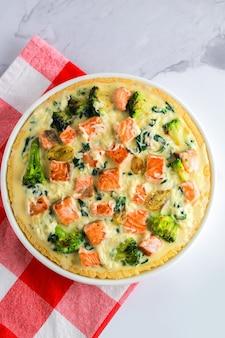 Classico tortino di pasta frolla al salmone e broccoli con infiorescenze di broccoli in salsa cremosa