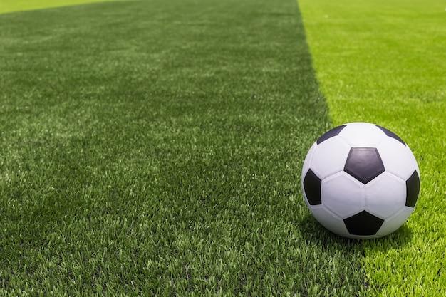 Pallone da calcio classico su erba artificiale luminosa e verde scuro