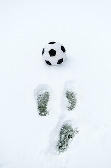 Pallone da calcio classico su un campo sportivo innevato e impronte nella neve. copia spazio, orientamento verticale