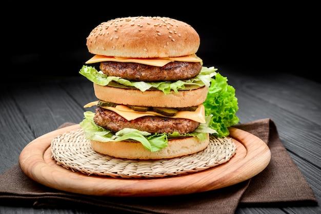 Un doppio cheeseburger in stile classico con due polpette di manzo, salsa, lattuga, formaggio, sottaceti e cipolle su un panino ai semi di sesamo