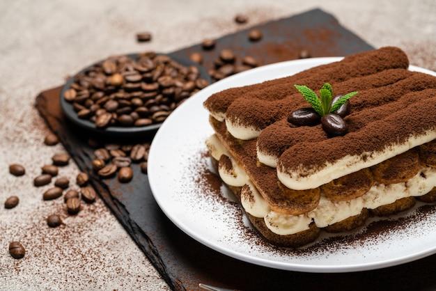 Dessert classico di tiramisù sul piatto ceramico su calcestruzzo