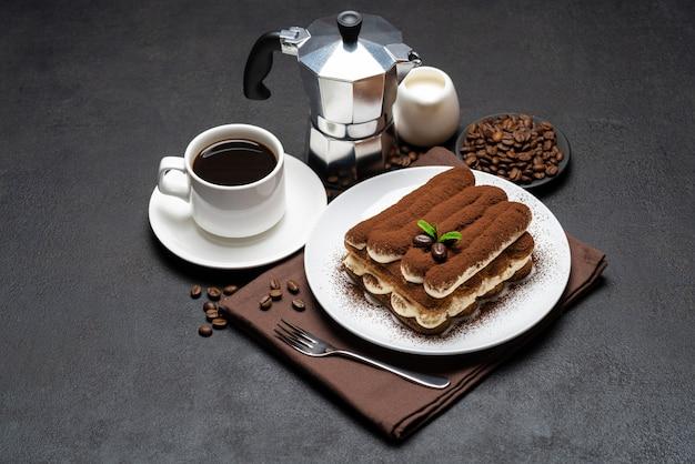 Dessert classico di tiramisù sul piatto ceramico, latte o crema e tazza di caffè sulla superficie di calcestruzzo