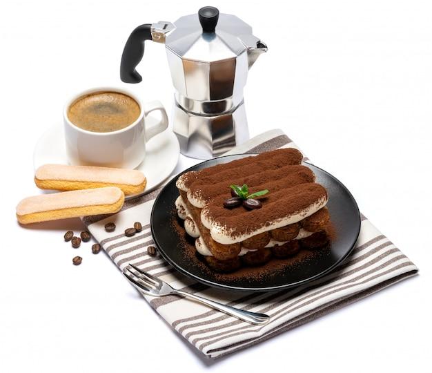 Dessert classico di tiramisù sul piatto ceramico, sui biscotti di savoiardi e sulla tazza di caffè isolati su superficie bianca con il percorso di ritaglio