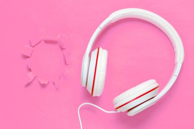 Cuffie classiche cablate bianche su sfondo di carta rosa con foro strappato
