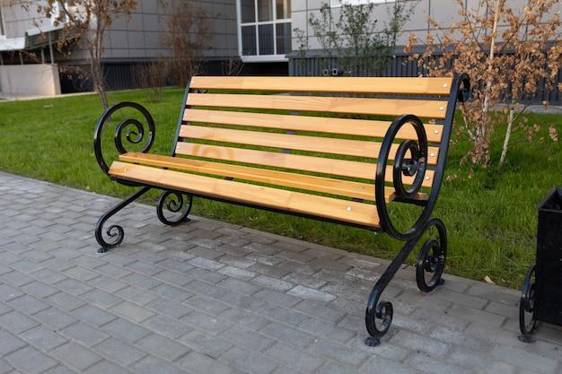 Panca classica in legno con braccioli in metallo vicino a un condominio. lastre per pavimentazione sotto il banco. miglioramento dello spazio pubblico nell'ambiente urbano.
