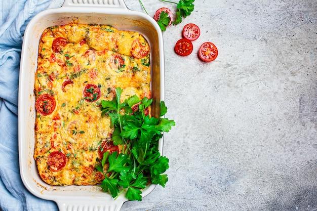 Frittata al forno classica o frittata con pomodori, peperoni e formaggio, sfondo grigio chiaro.