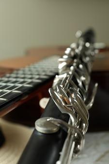 Chitarra classica, clarinetto e cappello, primo piano e messa a fuoco selettiva.