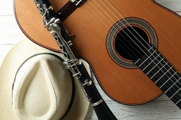 Chitarra classica, clarinetto e cappello sul tavolo di legno bianco