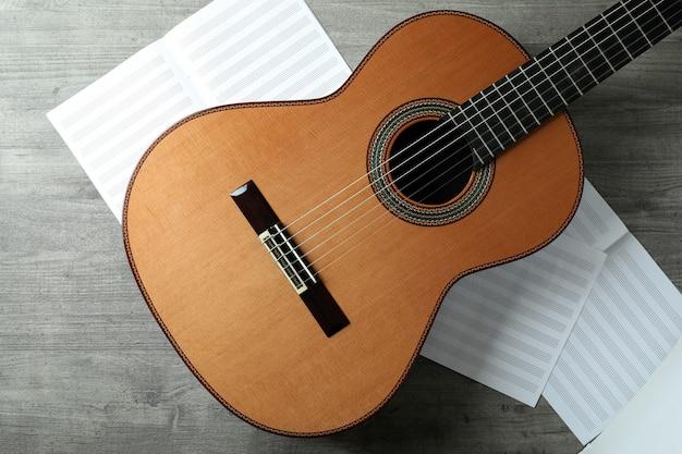 Chitarra classica e spartiti su tavolo grigio strutturato