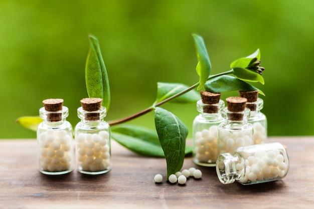 Globuli dell'omeopatia classica in bottiglie vintage e foglie della natura