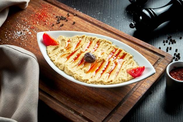 Piatto orientale classico - hummus di ceci con pomodori secchi in un piatto bianco su un tavolo scuro