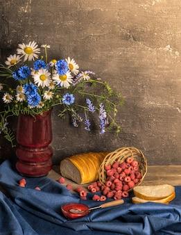 Classica natura morta con lampone raccolto estivo, pane e fiori