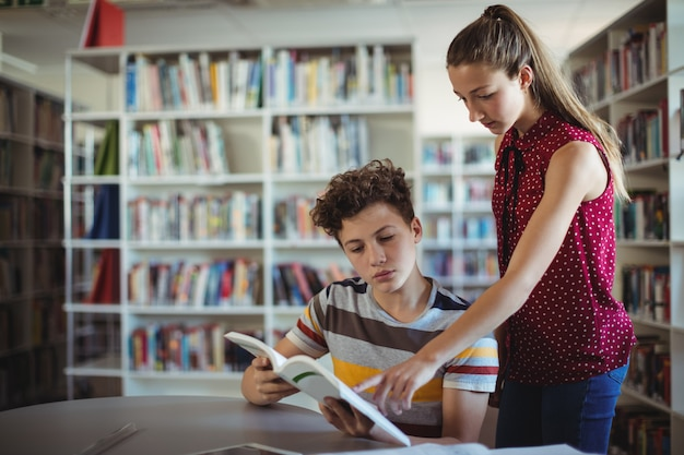 Compagni di classe che leggono un libro in biblioteca