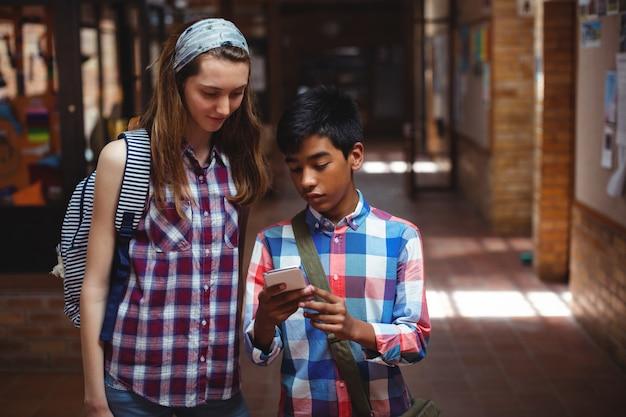 Compagni di classe che utilizzano il telefono cellulare nel corridoio a scuola