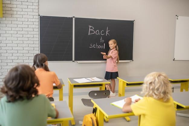 Nella classe. ragazza carina in maglietta rosa in piedi alla lavagna e la scrittura