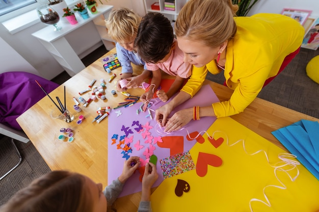 Decorazione della classe. gli alunni si sentono coinvolti mentre tagliano le farfalle per la decorazione della classe con l'insegnante
