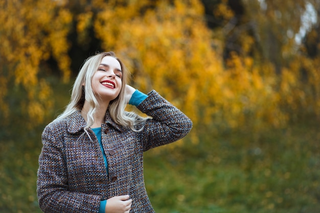 Elegante donna bionda con le labbra rosse che indossa un cappotto elegante che si gode il tempo nella foresta autunnale. spazio vuoto