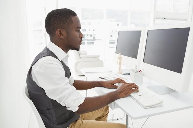 Uomo d'affari di classe che si concentra e che utilizza il computer