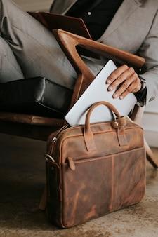 Uomo d'affari di classe che mette il suo laptop nella sua borsa di pelle marrone