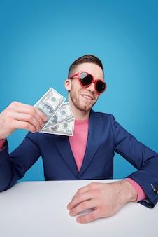 Elegante giovane uomo ricco in giacca blu e occhiali da sole glamour in possesso di tre banconote in dollari mentre era seduto alla scrivania