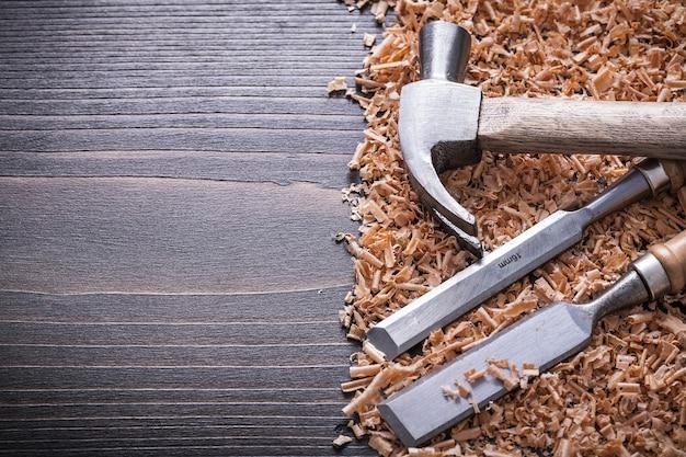 Scalpelli piatti martello da carpentiere e trucioli di legno su tavola di legno d'epoca
