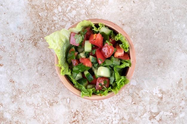 Una ciotola di argilla piena di insalata di verdure miste fresche su una superficie di pietra.