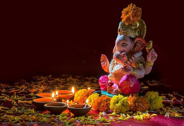 Le lampade di diya di argilla illuminate con lord ganesha durante la celebrazione di diwali. biglietto d'auguri design indian hindu light festival chiamato diwali