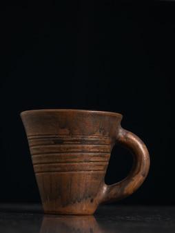 Tazza di argilla con manico su sfondo nero. ceramiche antiche.