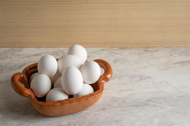 Pentola di terracotta piena di uova bianche su una barra di marmo e fondo in legno