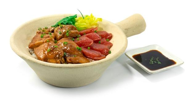 Il riso in pentola di terracotta con pollo e salsiccia cinese dolce stile hong kong decora la vista laterale di verdure di bok choy