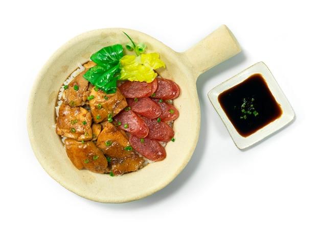 Il riso in pentola di terracotta con pollo e salsiccia cinese dolce stile hong kong decora la vista dall'alto di verdure bok choy