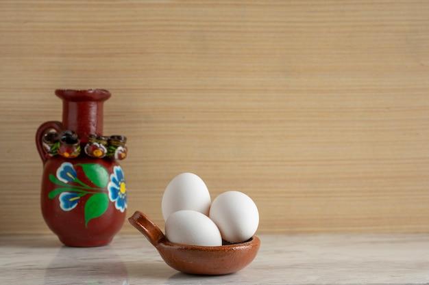 Pentola di terracotta con 3 uova bianche e una brocca di argilla decorata su una barra di marmo e fondo in legno