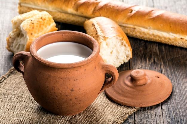 Pentola di terracotta con latte e baguette su tavola di legno