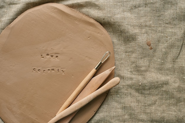 Lastra di argilla con strumenti in legno per artigianato fatto a mano con spazio copia in ceramica d'amore impronta
