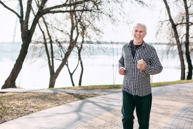 Aria pulita. uomo anziano vigoroso che corre e ascolta la musica