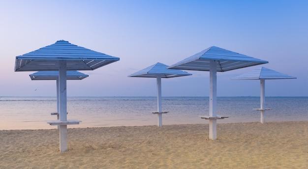 Spiaggia pulita con ombrelloni in legno, e il cielo azzurro della sera