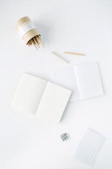 Taccuino in bianco pulito, matite e temperamatite su bianco