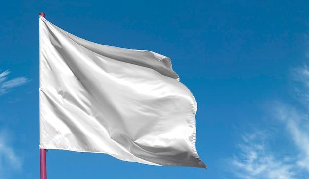 Pulisca la bandiera bianca in bianco sull'asta della bandiera contro il cielo blu,