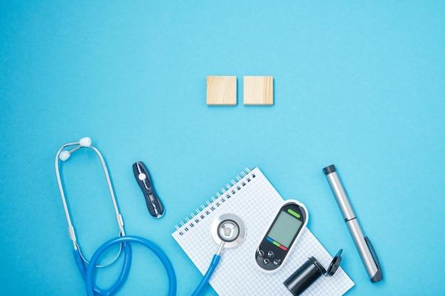 Blocco pulito con molla, stetoscopio, glucometro, lancetta e penna a siringa con insulina su sfondo blu, concetto di giorno daibet, diagnosi del diabete